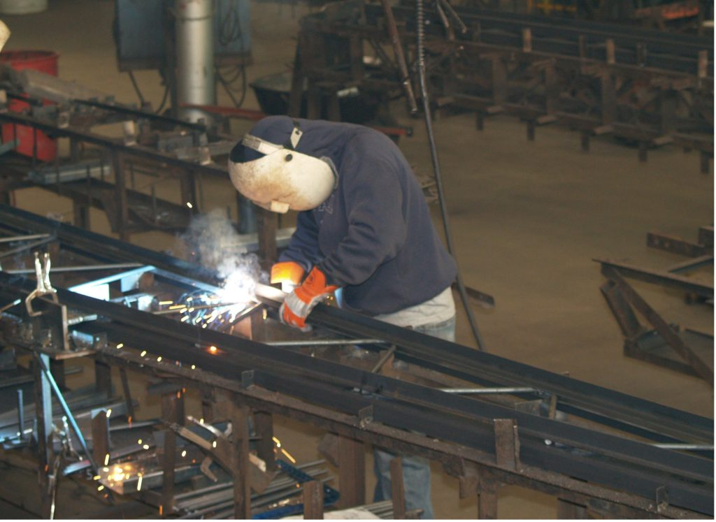 a worker welding a steel truss