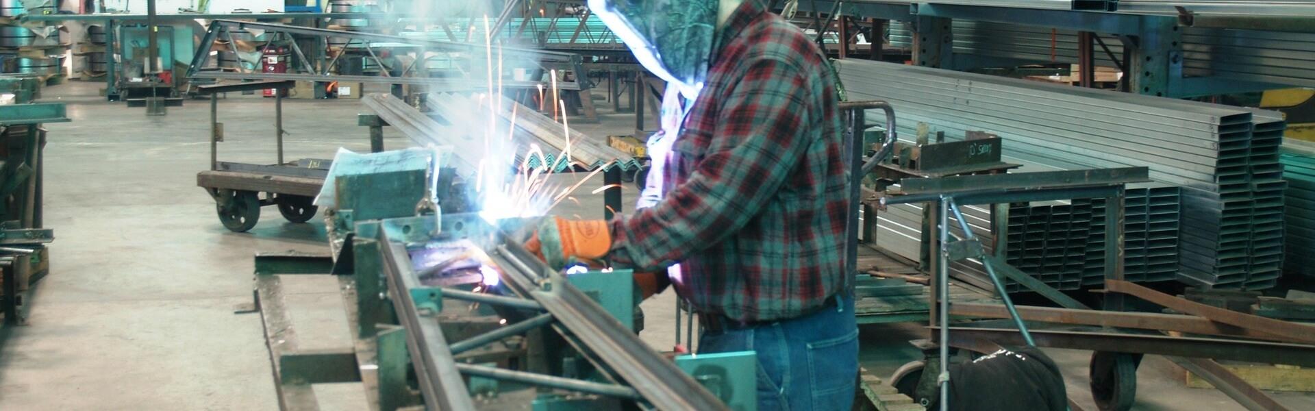 worker welding a steel truss arm